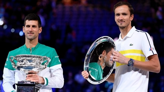 Serbia's Novak Djokovic (L) holds the Norman Brookes Challenge Cup after defeating Russia's Daniil Medvedev (R) in the men's singles final at the Australian Open(AP)