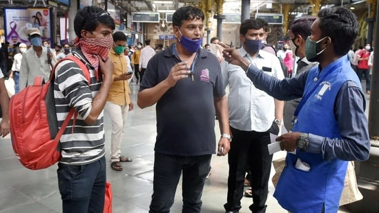 A BMC official collects fine from commuters for not wearing face masks, at CSMT, in Mumbai on Saturday.(PTI Photo)