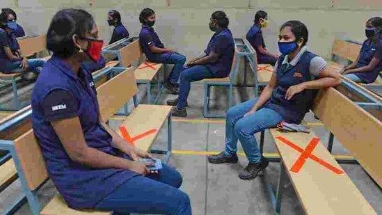 Industrial workers sit while maintaining social distancing at an assembly unit of Royal Enfield motorcycles in Oragadam on June 9.(AFP File Photo)