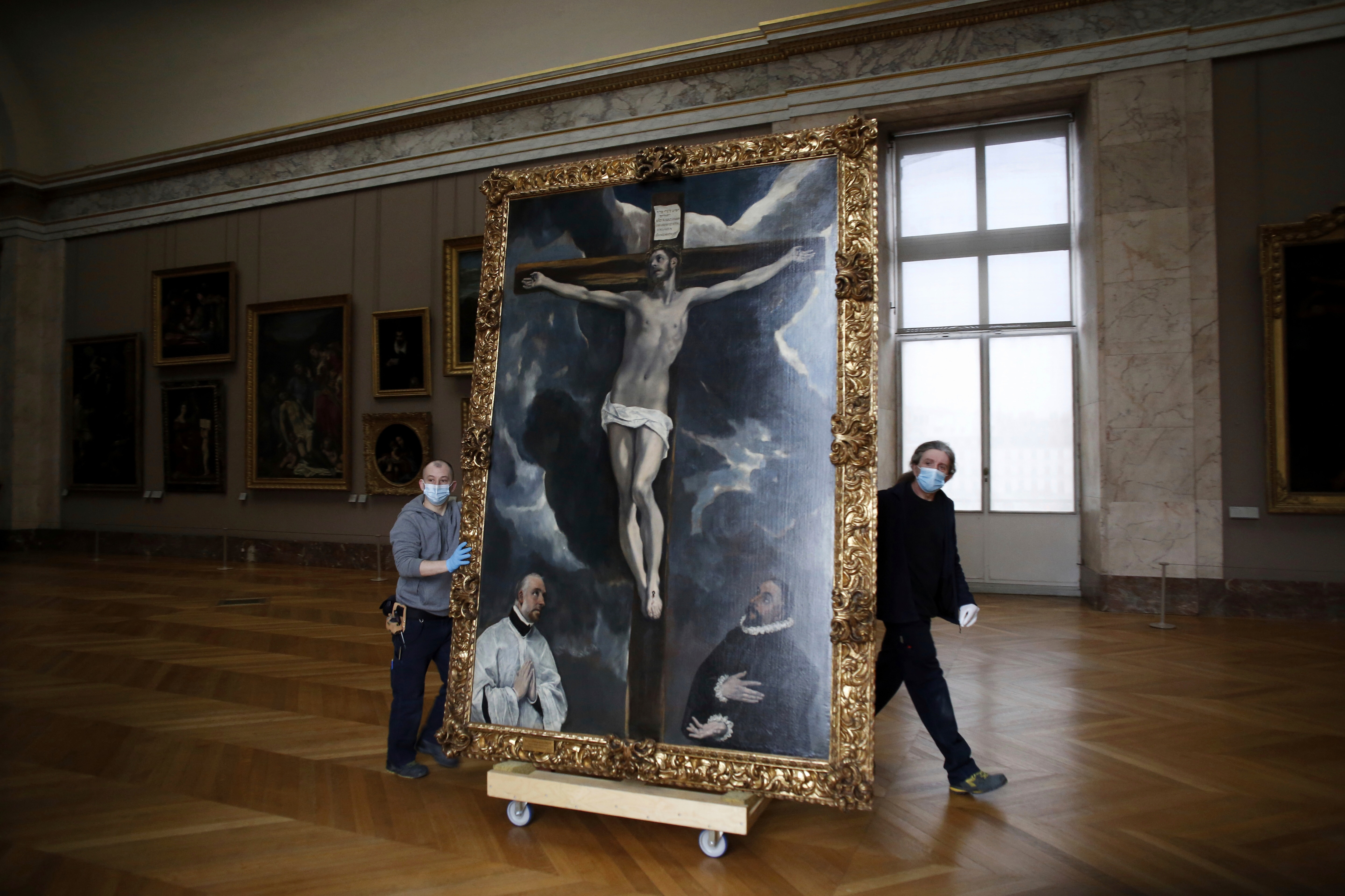 Workers at the Louvre museum transport a painting called Christ on the Cross Adored by Two Donors by Spanish painter El Greco.(AP)