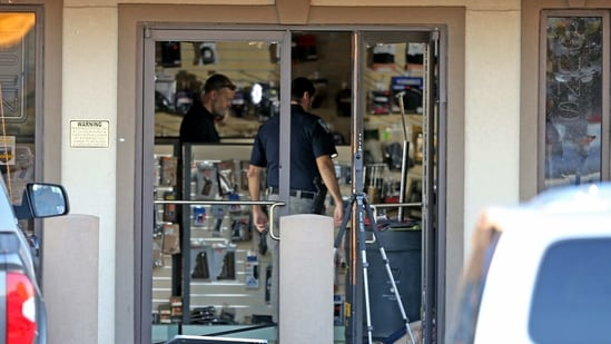 A body lies just inside the shattered front door at the Jefferson Gun Outlet as investigators work the scene in Metairie, Louisiana. (AFP)
