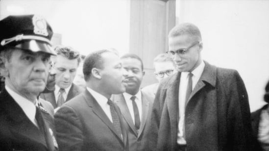 Martin Luther King Jr. and Malcolm X (R) wait for a press conference to begin in an unknown location, March 26, 1964 in this file photo. (AFP)