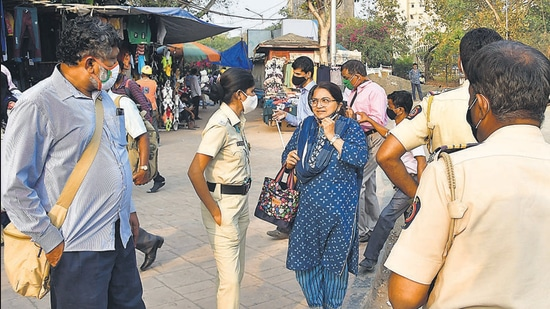 Mumbai Police team takes action against a citizen caught without a mask outside Churchgate station on Monday. (Bhushan Koyande/HT)
