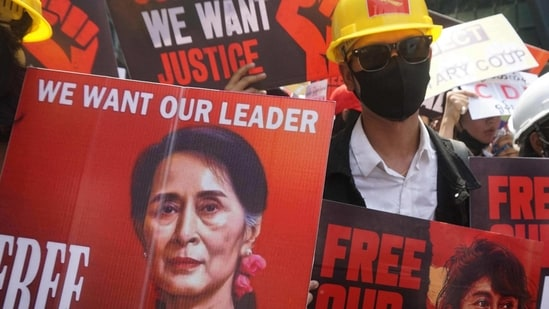 Protesters hold signs calling for the release of detained Myanmar civilian leader Aung San Suu Kyi during a demonstration against the military coup in Yangon on February 21, 2021.