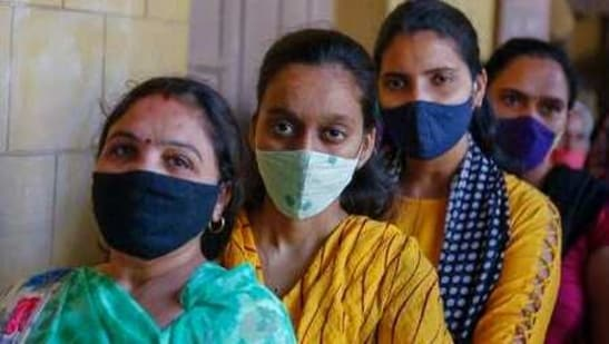 Indian women wearing face masks as precaution against COVID-19, stand in queue to cast their vote for local body elections in Ahmedabad, India, Sunday, Feb. 21, 2021. (AP Photo/Ajit Solanki)(AP)
