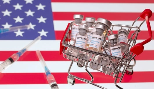 """A small shopping basket filled with vials labeled """"COVID-19 - Coronavirus Vaccine"""" and medical syringes are placed on a US flag in this illustration photo.(REUTERS)"""
