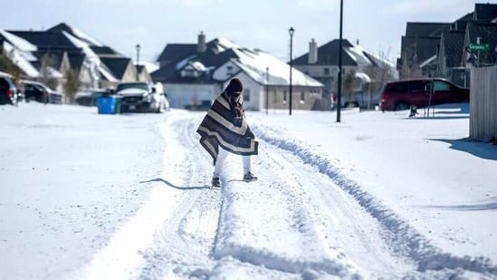A man walks to his friend's home in a neighbourhood without electricity as snow covers the BlackHawk neighborhood in Pflugerville, Texas, US.(Reuters)