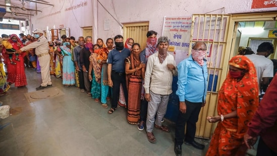 Voters stand in a queue to cast their vote at a polling centre during Gujarat Municipal Elections, in Ahmedabad, Sunday.