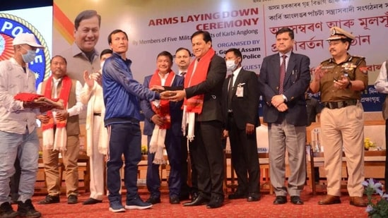Chief of militant outfit Peoples' Democratic Council of Karbi Longri (PDCK) IK Songbijit (in blue jacket) handing over arms to Assam Chief Minister Sarbananda Sonowal at a ceremony in Guwahati on Tuesday(HT PHOTO)