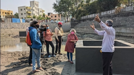 Groundwater expert Shashank Deshpande explains to residents the designs of a percolation pond.