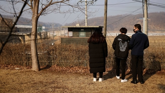 A North Korean defector and his children stand in front of a barbed wire fence near the demilitarised zone separating the two Koreas, in Paju,(Reuters)