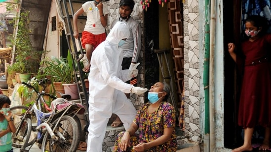 A BMC health worker wearing protective gear takes a swab sample of a woman for the Covid-19 test at Dharavi, in Mumbai on Tuesday. (ANI Photo)