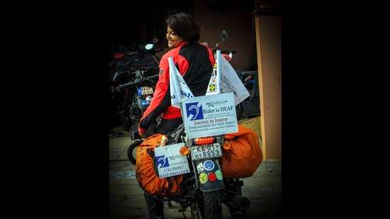 Bangalorean Bon her bike that has a sign board reading: Rider is deaf.
