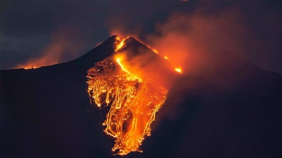 The moon is partially seen in the sky as lava flows from the Mt Etna volcano, near Catania in Sicily, southern Italy,(AP)