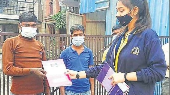 School students distribute home-made face masks among people from the weaker sections of society.