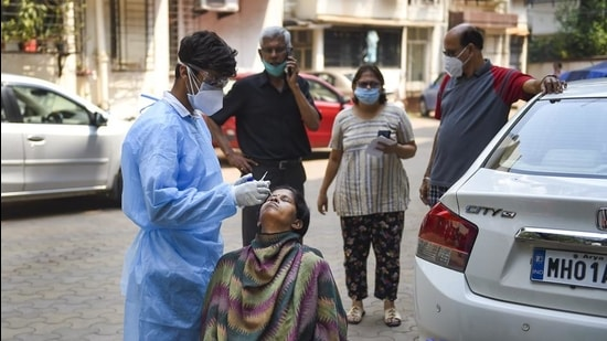 A BMC health worker takes a sample from a woman for Covid-19 test, at a housing society in Dadar, Mumbai on February 24. (PTI)