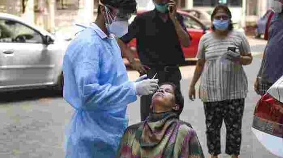 A health worker takes a sample from a woman for Covid-19 test (PTI)