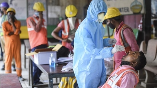 A BMC health worker collects swab sample of a construction worker for Covid-19 test, at Siddhivinayak Metro site in Mumbai on February 25. (PTI)
