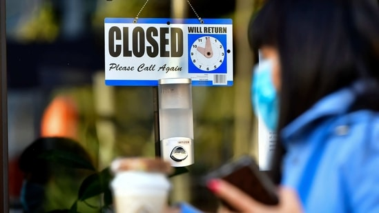 A pedestrian wearing her facemask and holding a cup of coffee walks past a closed sign hanging on the door of a small business in Los Angeles, California.(AFP)