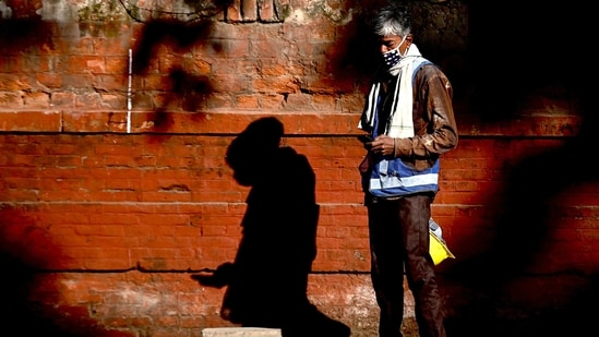 =A worker looks at his mobile as he stands on a footpath near a construction site in New Delhi.(AFP)