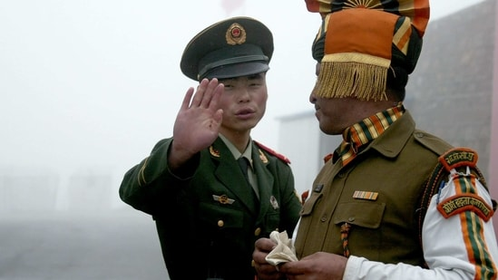 A Chinese soldier gestures next to an Indian soldier at the Nathu La border crossing between India and China in India's northeastern Sikkim state(AFP/File Photo)