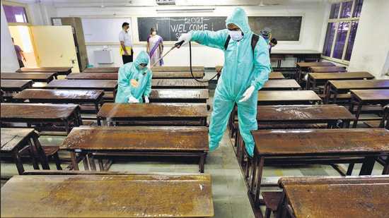 Workers sanitise a classroom at SIES College in Sion, Mumbai. (HT FILE)