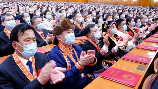 In this photo released by China's Xinhua News Agency, attendees applaud during a ceremony to mark the official end of extreme poverty in China held at the Great Hall of the People in Beijing,(AP)