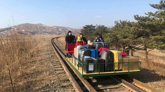 Russian diplomats and family members use a hand-pushed rail trolley to leave North Korea amid Covid-19 restrictions.(via REUTERS)