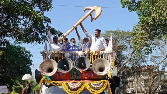 Delhi CM Arvind Kejriwal and Aam Aadmi Party leaders hold a plough as they participate in a roadshow, in Surat on Friday. (ANI Photo)