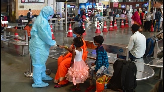 A health worker screens inbound travellers at CSMT. (Bhushan Koyande / HT Photo)