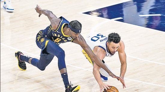 Indiana Pacers' Justin Holiday (8) and Golden State Warriors' Stephen Curry (30) dive for the ball during the second half of an NBA basketball game Wednesday, Feb. 24. (AP)