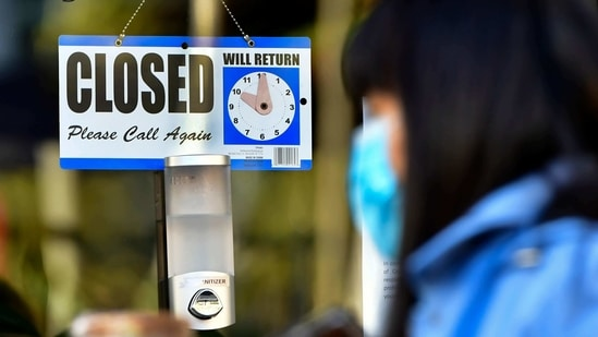 A pedestrian wearing her facemask and holding a cup of coffee walks past a closed sign hanging on the door of a small business in Los Angeles, California.