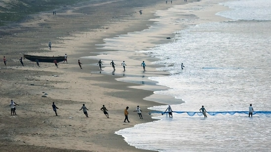 Fishermen pull a long net after fishing in the Bay of Bengal at Jodugulla Palem Beach, in Visakhapatnam on Thursday. (ANI Photo)