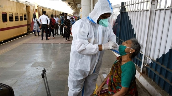 A health worker wearing a PPE kit collects a swab sample of an old lady for the COVID-19 test as she arrives at Dadar railway station, in Mumbai on Friday. (ANI Photo)