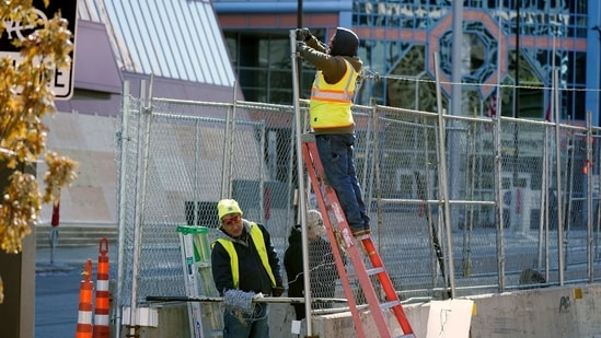Workers install barbed wire on fencing outside the Hennepin County Government Center, Wednesday, Feb. 23, 2021 in Minneapolis.(AP)