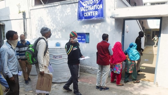 Sanitation workers stand in a queue to receive the first dose of vaccine in Delhi.(PTI )