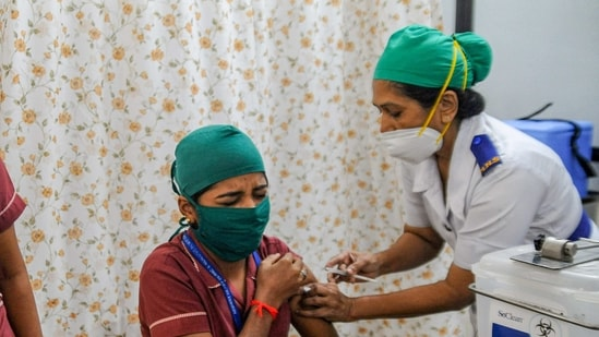 A medic administers the first dose of Covid-19 vaccine to a frontline worker during a Covid-19 inoculation drive.(PTI)