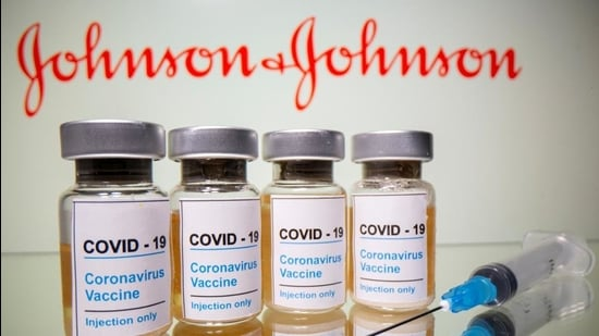 """Vials with a sticker reading, """"COVID-19 / Coronavirus vaccine / Injection only"""" and a medical syringe are seen in front of a displayed Johnson & Johnson logo in this illustration taken October 31, 2020. (REUTERS FILE)"""