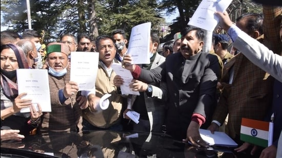Himachal Pradesh Congress MLAs holding up copies of the governor Bandaru Dattatreya's address and obstructing his exit from the assembly by standing in front of his car on Friday. They claimed he did not address issues such as inflation, unemployment and other concerns of the state in his speech. (Deepak Sansta/HT)