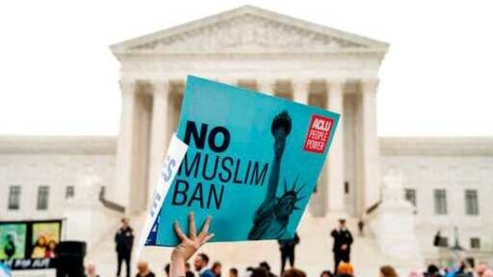 """A person holds up a sign that reads """"No Muslim Ban"""" during an anti-Muslim ban rally as the Supreme Court hears arguments.(AP)"""