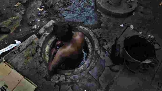 Municipal worker attempts to unblock a sewer overflowing with human excreta in New Delhi. Although a law bans manual scavenging - the manual removal of human excreta from 'dry toilets' - the practice is widespread across cities and towns in India.(Photo: Raj K Raj / Hindustan Times)