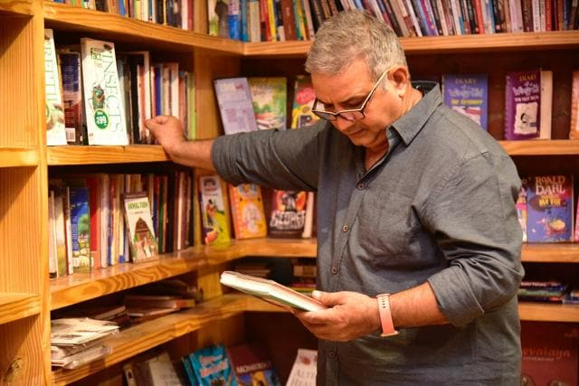 Kumud Mishra browsing through books at Repertwahr Performance Cafe (Sourced)