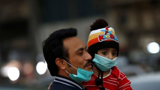 A man and child with protective masks walk outside a market as the coronavirus disease (Covid-19) pandemic continues, in Karachi, Pakistan.(Reuters)