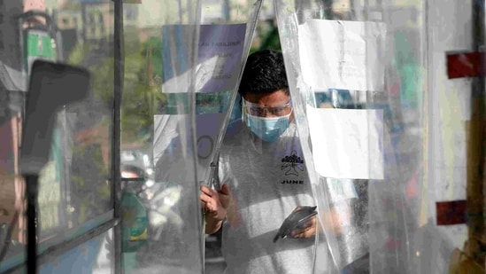 A man wearing a face mask and a face shield as protection against the coronavirus disease (Covid-19) enters a disinfection booth at a community quarantine checkpoint, in Pasay, Metro Manila, Philippines. (Reuters)
