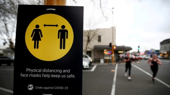 People jog past a social distancing sign on in New Zealand's Auckland in this file picture. (REUTERS)