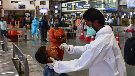 A health worker wearing protective gear takes a nasal swab sample of inbound travellers for Covid-19 tests at CSMT railway station in Mumbai.(Bhushan Koyande/HT Photo)