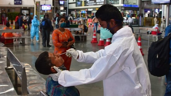 A health worker wearing protective gear takes a nasal swab sample of inbound travellers for Covid-19 coronavirus tests at CSMT railway station, in Mumbai.(Bhushan Koyande / HT file photo)