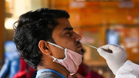 A medical worker takes a swab sample from a passenger for a Rapid Antigen Test (RAT) Covid-19 coronavirus test at the railway station in New Delhi.