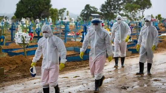 Workers wearing protective suits walk past the graves of Covid-19 victims at the Nossa Senhora Aparecida cemetery, in Manaus, Brazil.(AFP)