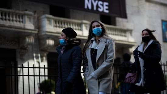 Women walk past the New York Stock Exchange (NYSE) near Wall Street in New York. (AFP)